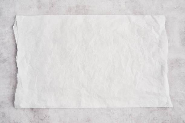 skrynklig bit vit pergament eller bakplåtspapper på grå betong bakgrund. - bakplåt bildbanksfoton och bilder