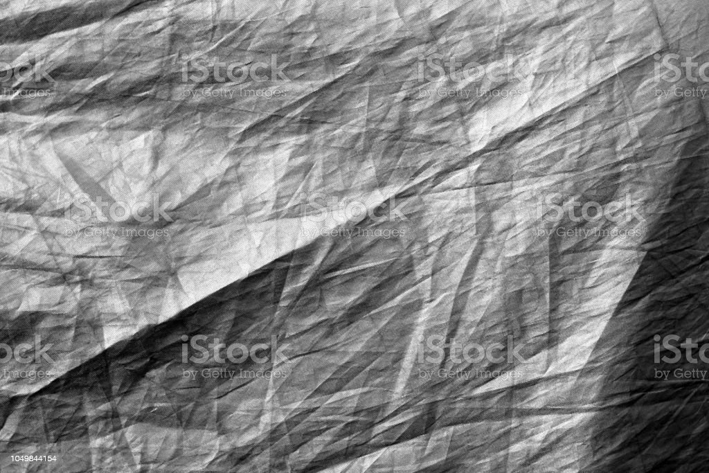 Crumpled plastic textile texture in black and white. stock photo