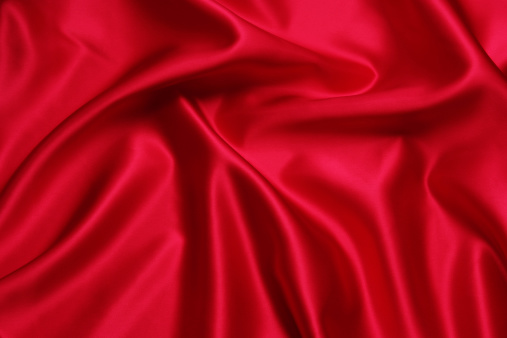 Close-up shot of crumpled red satin texture background.