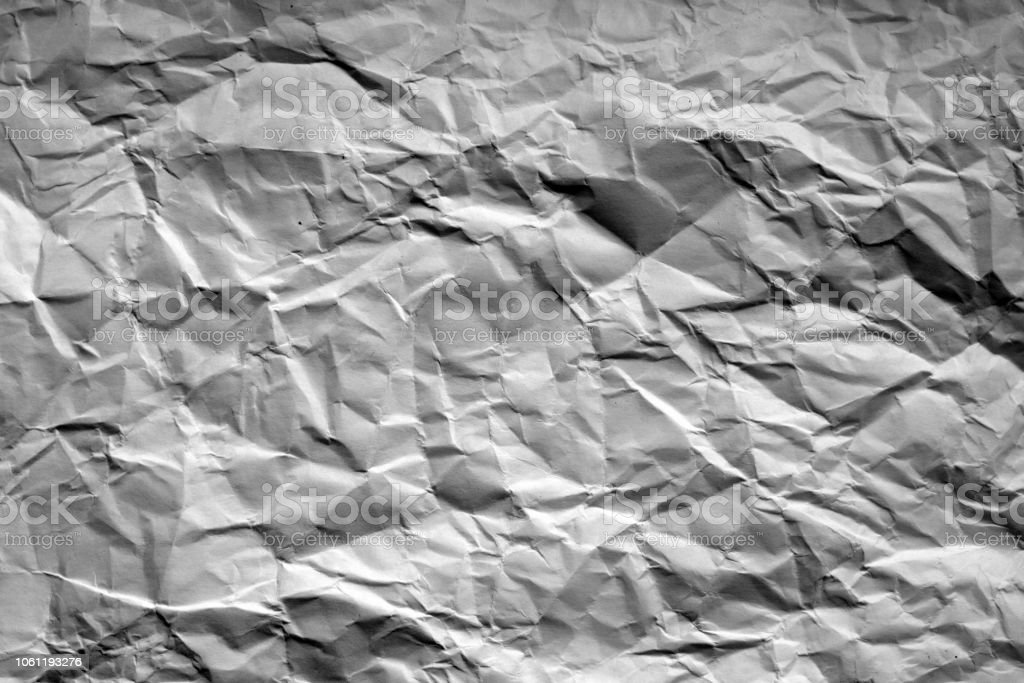 Crumpled sheet of paper with blur effect in black and white. stock photo