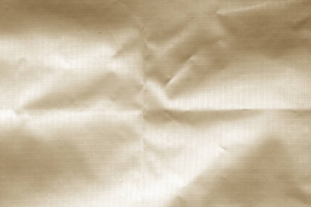 crumpled transparent plastic surface in brown color. - nylon texture stock pictures, royalty-free photos & images