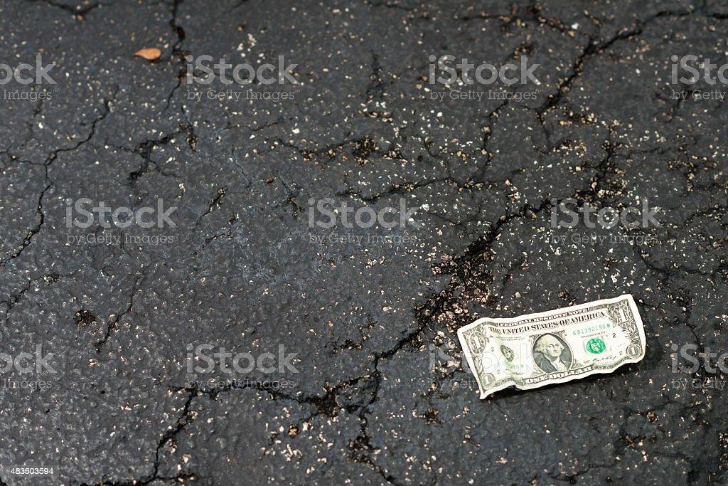 Crumpled US Dollar Bill on Asphalt stock photo