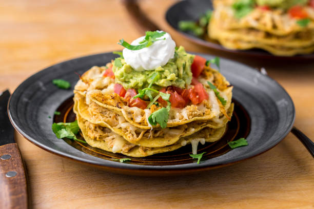 Crunchy chicken tostada stack. Crunchy chicken tostada stack. Tostadas are a type mexican food, made with crispy fried corn tortillas covered with layers of various ingredients such as chicken, guacamole, cheese, sour cream & salsa sour cream stock pictures, royalty-free photos & images