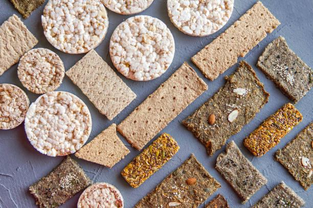 knusprige knäckebrot auf grauem hintergrund - zuckerfreie lebensmittel stock-fotos und bilder