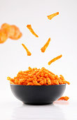 istock crunchy stick corn chips in black bowl on white background 1195635448