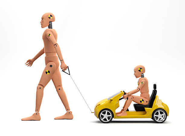 A crush test dummy pulling a car with a smaller dummy stock photo
