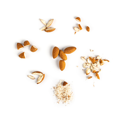 Crushed almonds isolated on white background closeup. Grated almond seeds and cut kernels collection