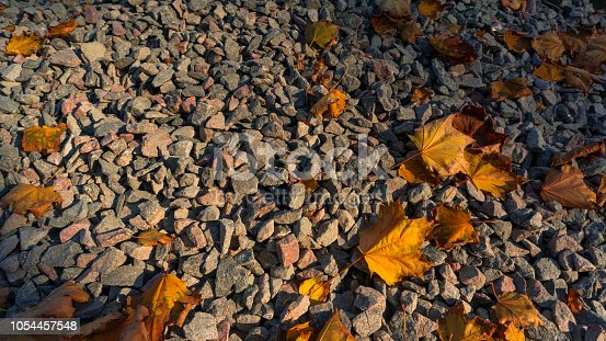 Crushed broken stone breakstone texture and background with fallen yellow leaves