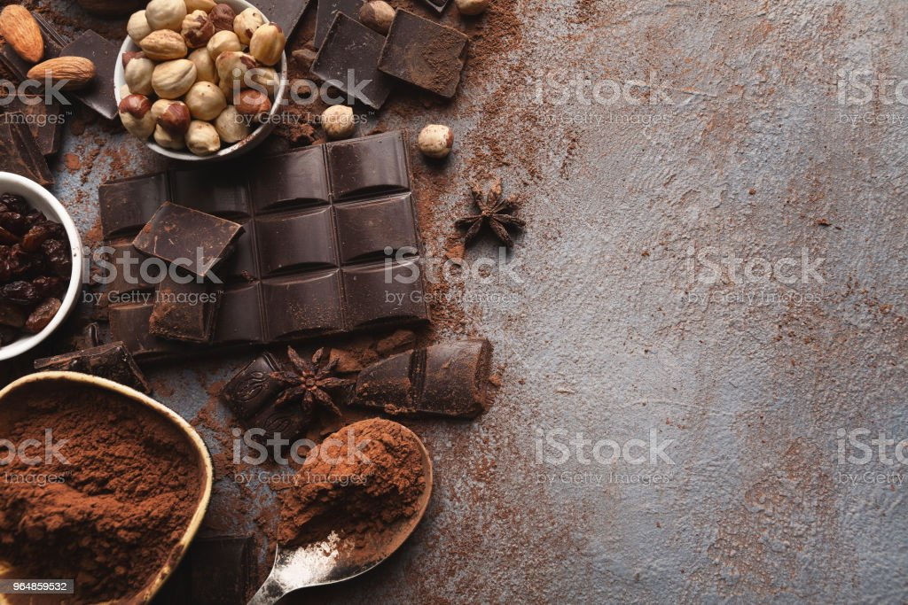 Crushed chocolate bar pieces and cocoa on gray background royalty-free stock photo