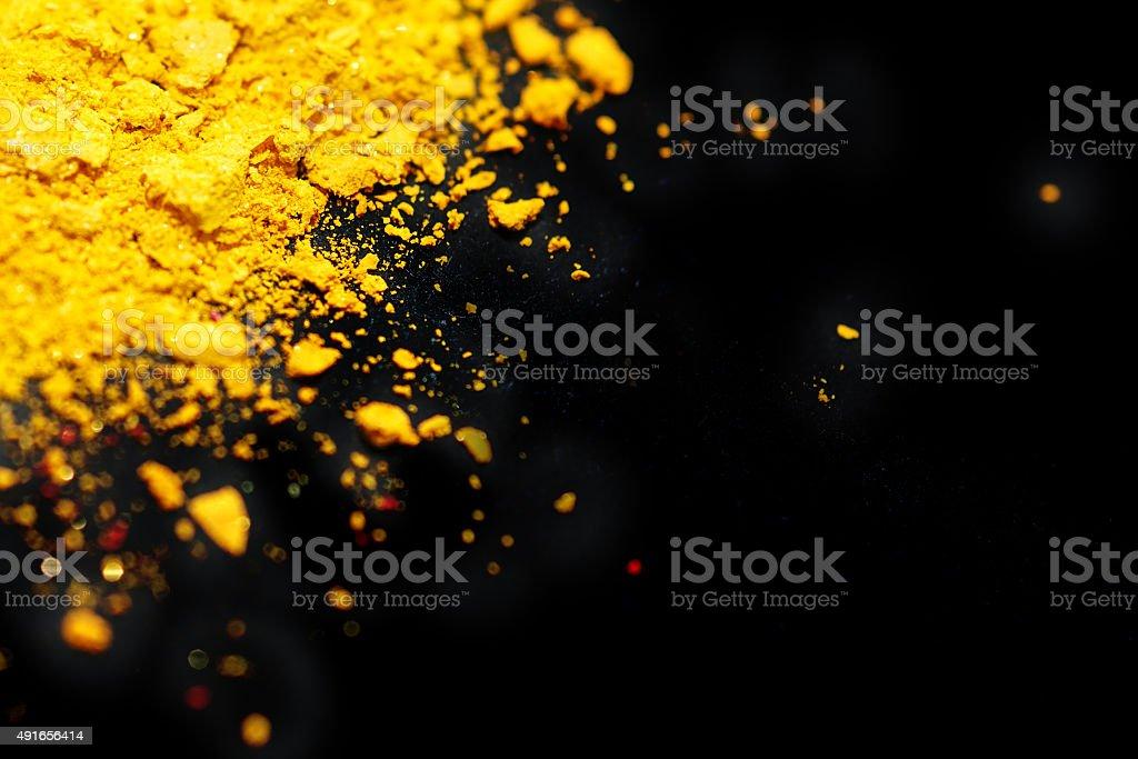 Crushed eyeshadow yellow color, Black background stock photo