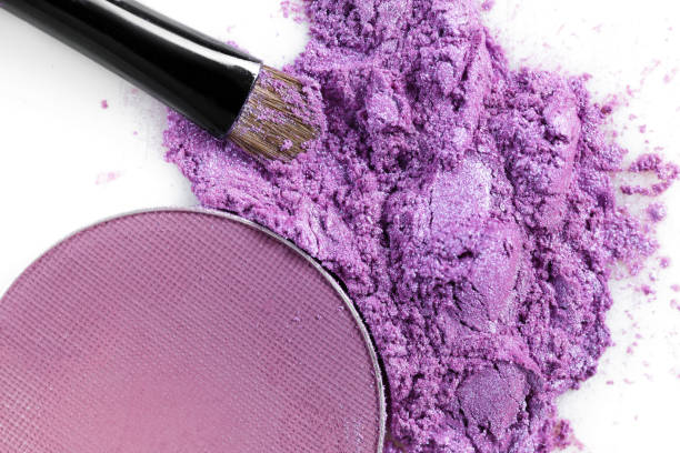 zerkleinerte lila lidschatten und make-up pinsel isoliert auf weißem hintergrund - lila augen make up stock-fotos und bilder