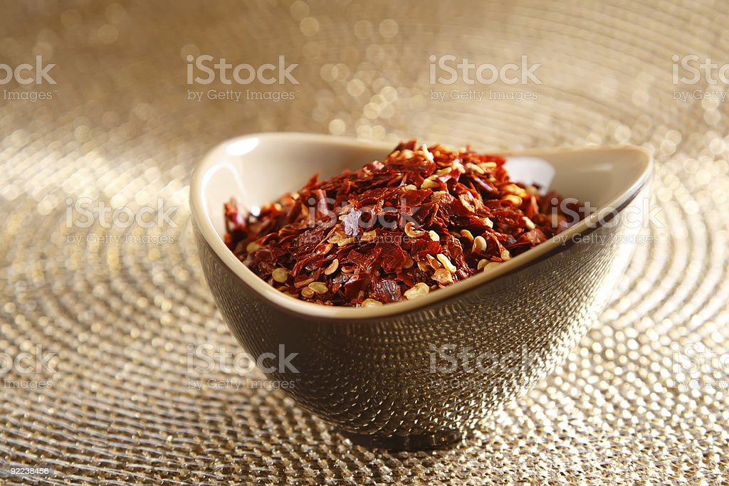 crushed red hot chilli pepper in bowl on golden royalty-free stock photo