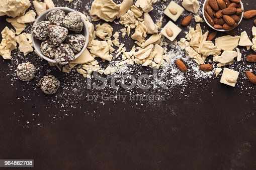 istock Crushed white chocolate pieces and truffles on dark background 964862708
