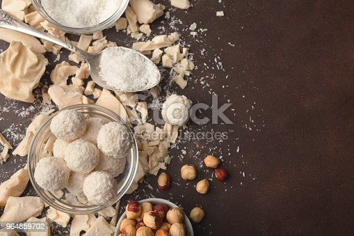 istock Crushed white chocolate pieces and truffles on gray background 964859702