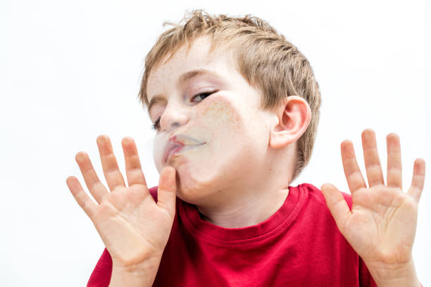 crushed young boy touching his goofy face to a window stock photo