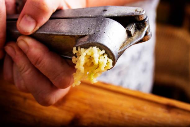 crushing garlic - aglio alliacee foto e immagini stock