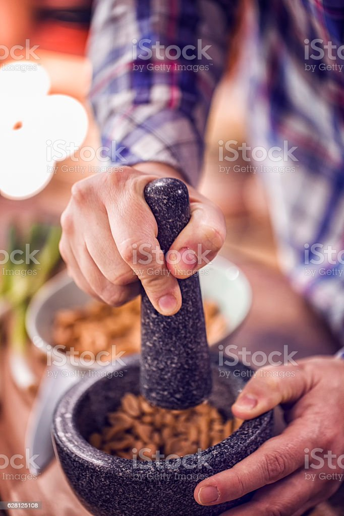Crushing Herbs and Peanuts in Pestle and Mortar stock photo