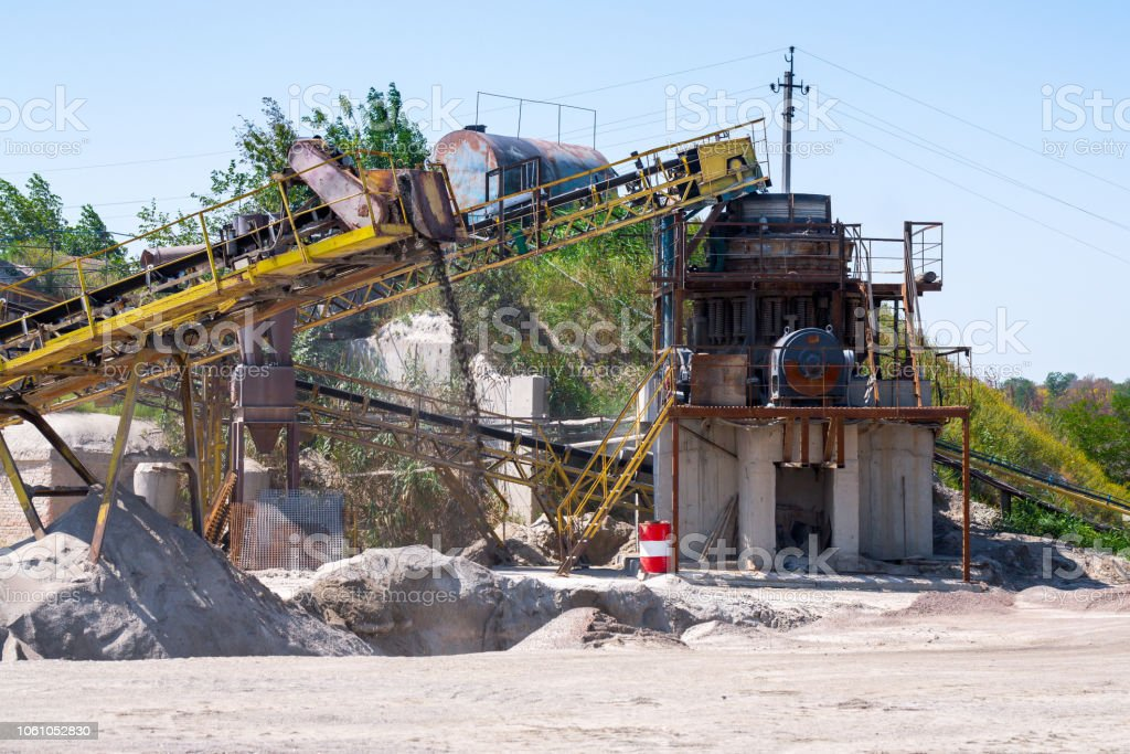 Crushing machinery, cone type rock crusher, conveying crushed granite gravel stone in a quarry open pit mining. Processing plant for crushed stone and gravel. Mining and Quarry mining equipment. stock photo