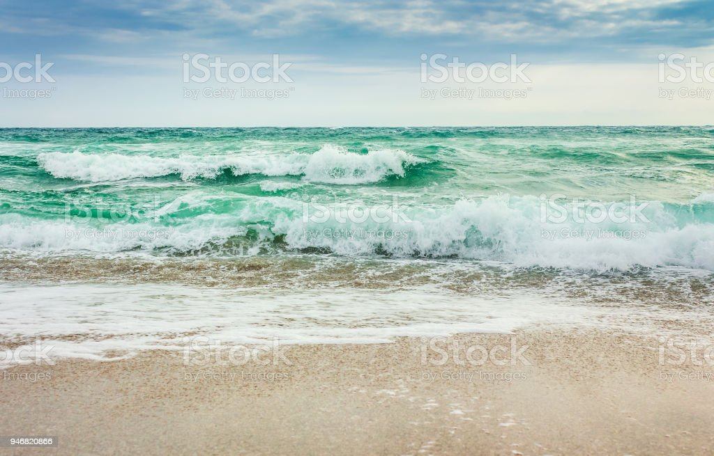 crushing waves on sandy beach stock photo