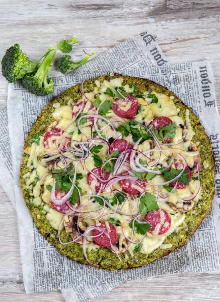 crust broccoli basis low carbs keto pizza mit salami, avocado auf vintage newspapper. ansicht von oben - low carb pizzateig stock-fotos und bilder