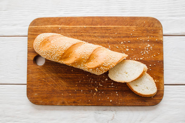 Crusty baguette on wooden board flat lay stock photo