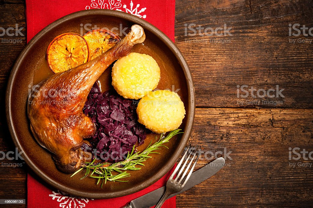 Crusty goose leg with braised red cabbage and dumplings stock photo