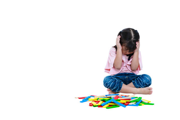 Crying asian child playing toys and seem unhappy. Isolated stock photo