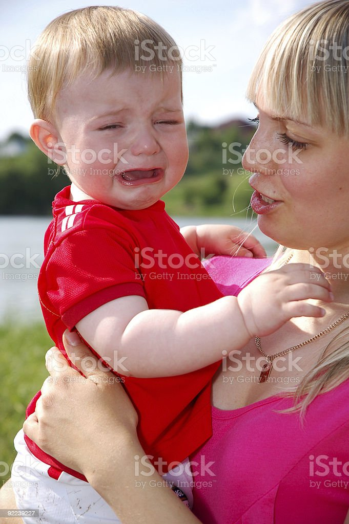 crying baby and his careful mom stock photo