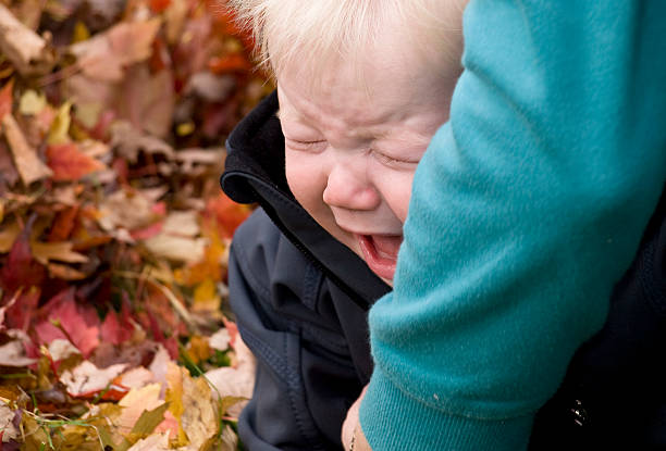 Crying baby boy gets a hug stock photo