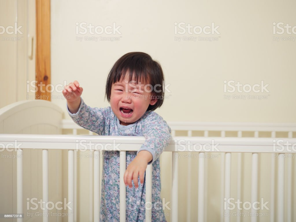 Crying baby girl in cot bed royalty free stock photo