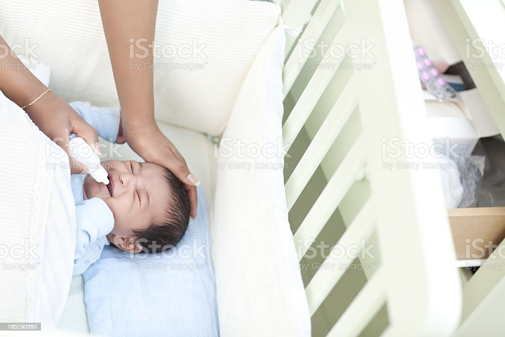 Crying baby receives medication. stock photo