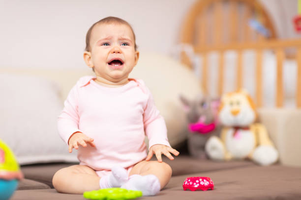 Crying baby sitting on the bed stock photo