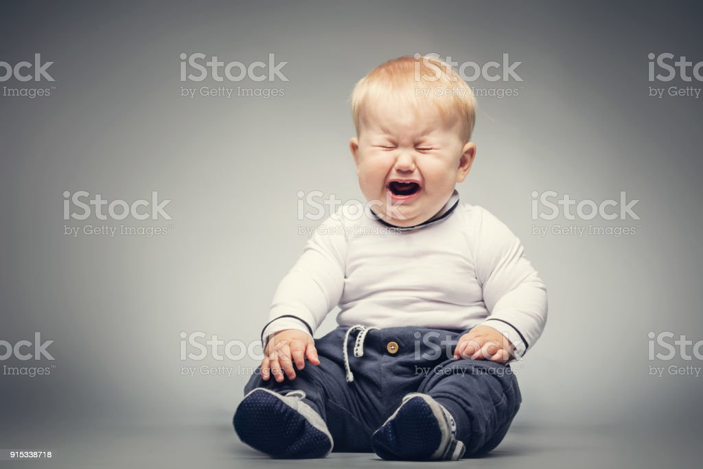 Crying baby sitting on the ground. stock photo