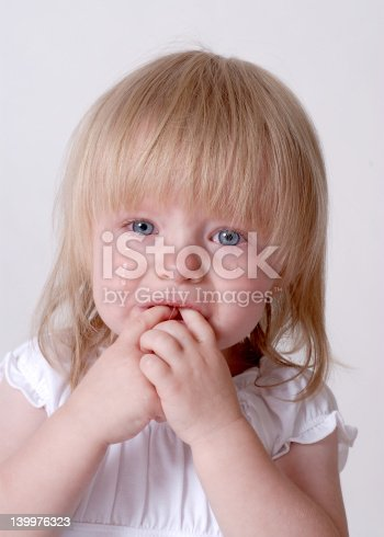 Crying baby toddler with hands in her mouth