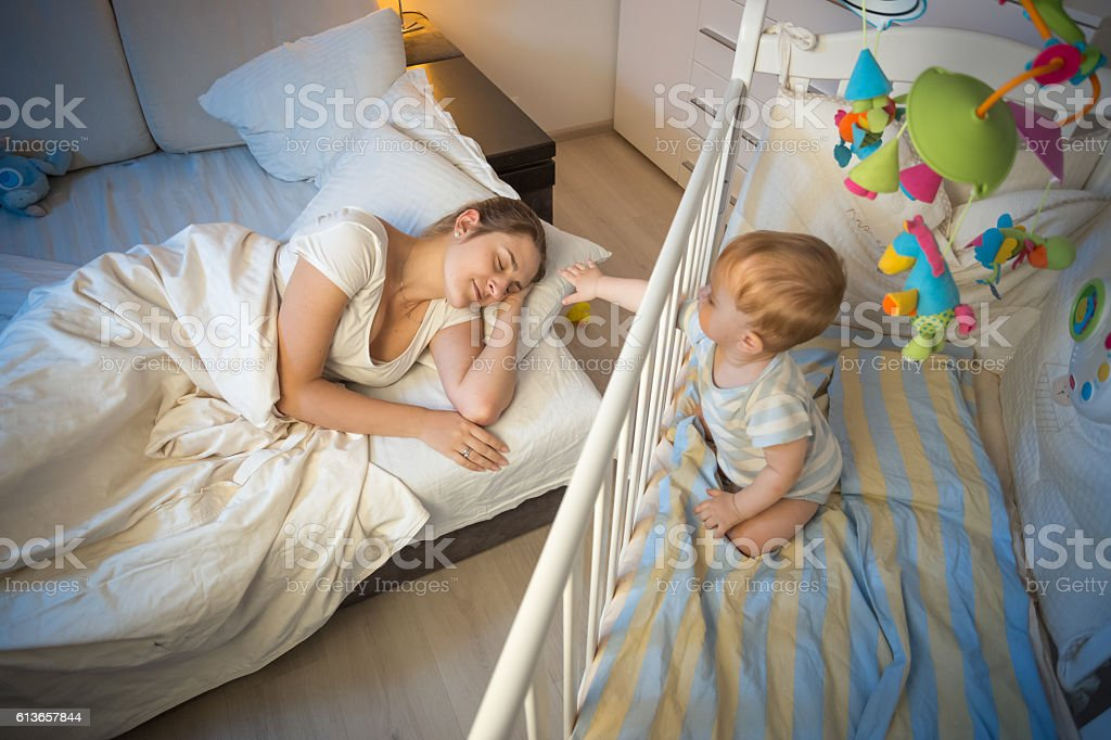 Crying baby waking up and reaching his mother at night stock photo