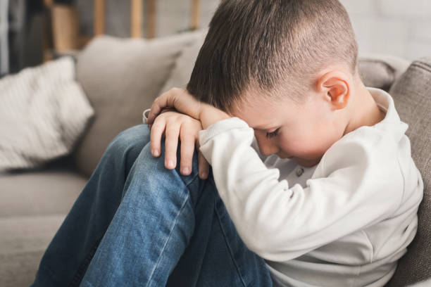 Crying child boy hugging his knees on sofa Crying child boy hugging his knees, sitting on sofa, closeup one boy only stock pictures, royalty-free photos & images