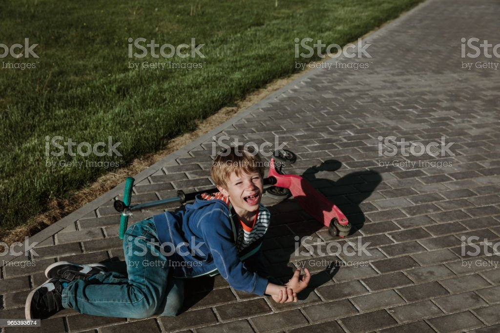 crying child fall off scooter, blood on his face royalty-free stock photo