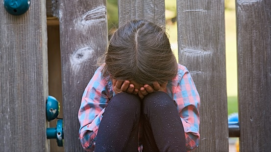 Crying caucasian child girl sitting on the floor covering his face