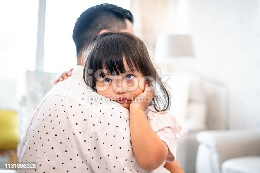 Cute Chinese girl crying on her father's shoulder.