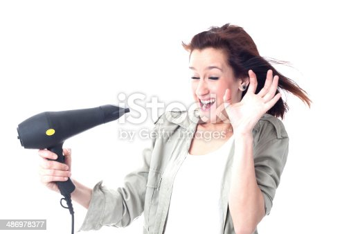 639833996istockphoto Crying girl holding hair dryer 486978377