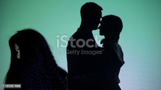 istock Crying girl turning head from silhouette couple kissing on background, betrayal 1183387669