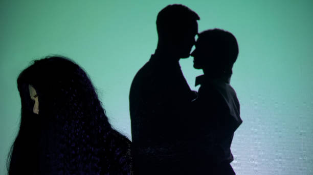 Crying girl turning head from silhouette couple kissing on background, betrayal stock photo