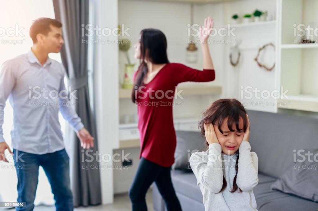 Crying girl with his fighting parents in the background, Sad girl while parents quarreling in the living room stock photo