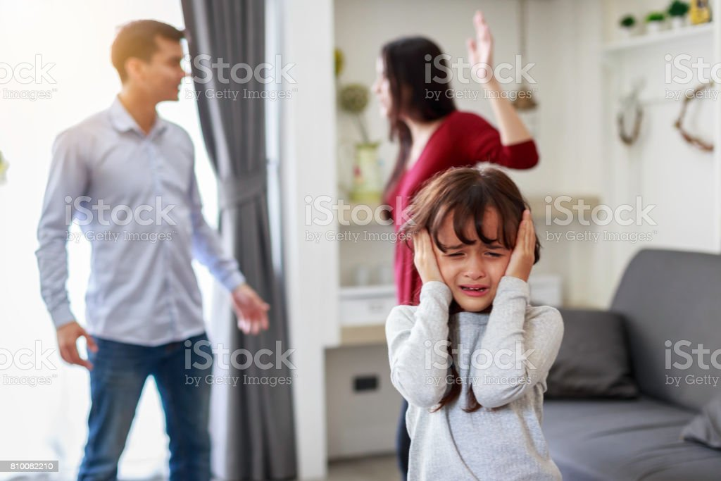 Crying girl with his fighting parents in the background, Sad gril while parents quarreling in the living room stock photo