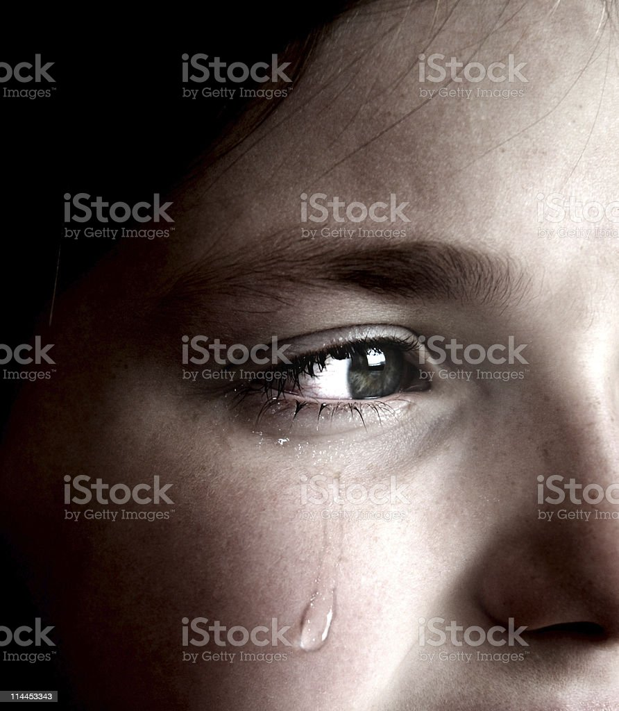 Crying girl with tear on cheek stock photo
