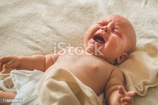 istock Crying hungry newborn baby lying on the bed. Love baby. Newborn baby and mother 1166365914