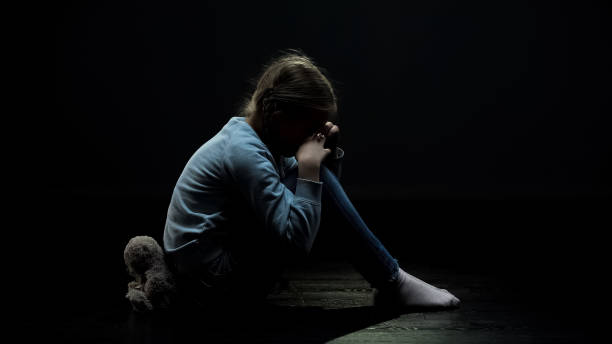 Crying little girl sitting back to teddy bear in dark abandoned room, loneliness stock photo