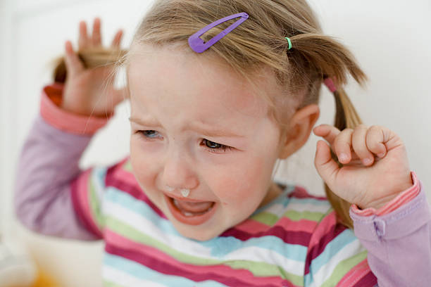 Crying little toddler, having a tantrum Crying little toddler, having a tantrum during a terrible two phase, raging in her crib. Childhood, growing up, developmental phase and parent patience concept. mucus stock pictures, royalty-free photos & images