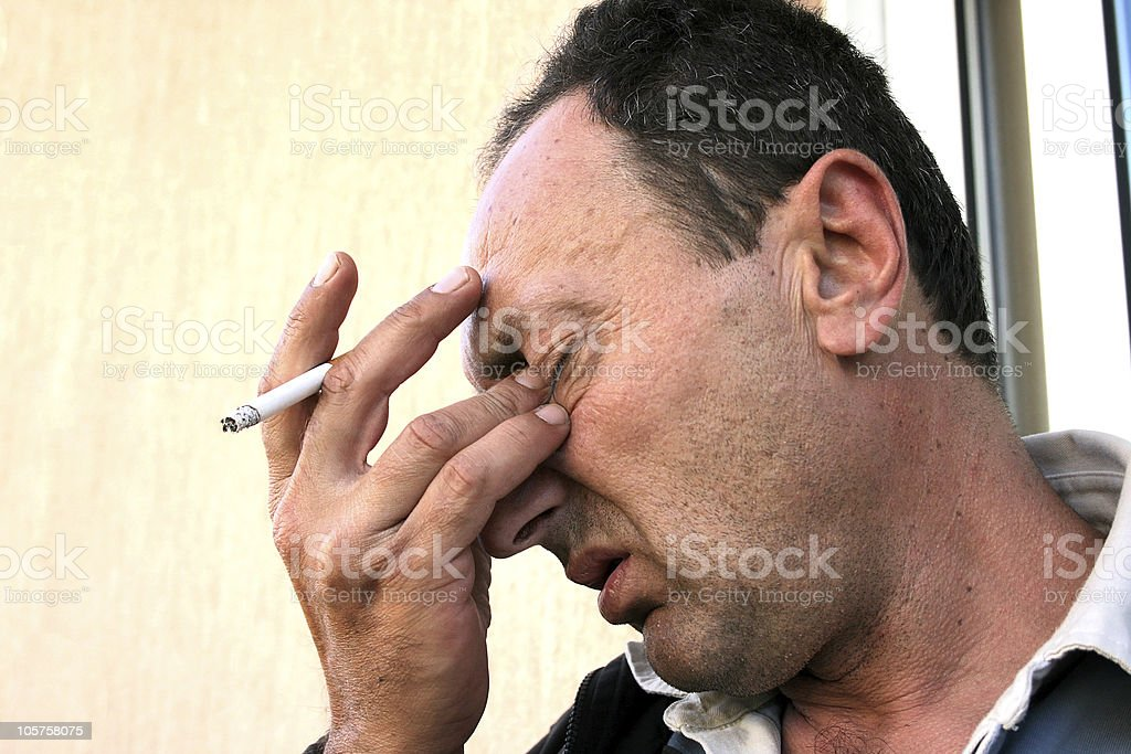 Crying man with cigarette stock photo