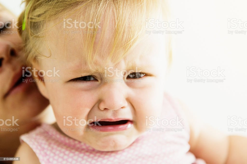 Crying one-year-old girl being soothed by mother in background stock photo